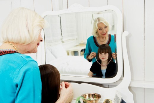 Grandmother (2-4) trying necklace on granddaughter (8-10) in mirror : Stock Photo