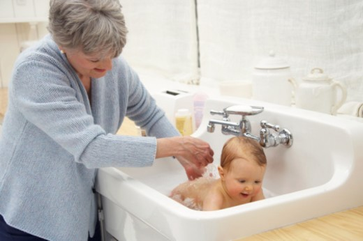 Grandmother bathing baby granddaughter (8-10 months) in sink, smiling : Stock Photo