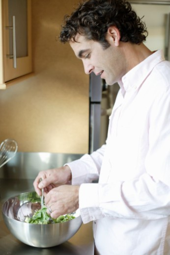 Stock Photo: 1527R-1096494 Man tossing salad in kitchen, side view, close-up