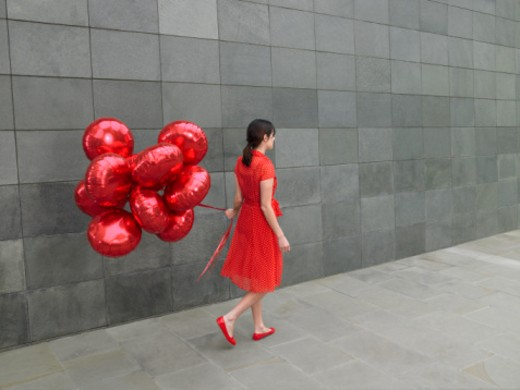 Young woman walking along with bunch of red foil balloons, rear view : Stock Photo