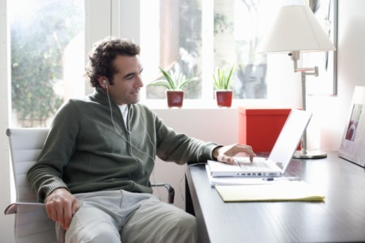 Man at desk, using laptop computer, wearing headphones, side view : Stock Photo