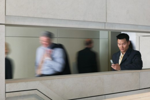 Businessman using mobile phone, people in background, (blurred motion) : Stock Photo