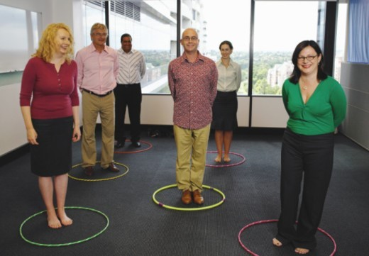 Business colleagues standing  plastic hoops, smiling : Stock Photo