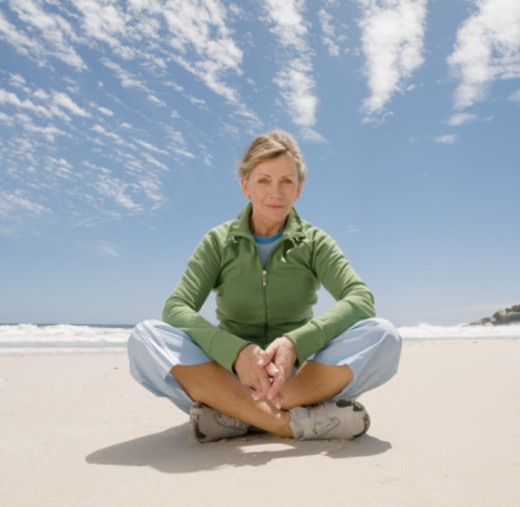 Mature woman sitting cross-legged on beach, portrait : Stock Photo