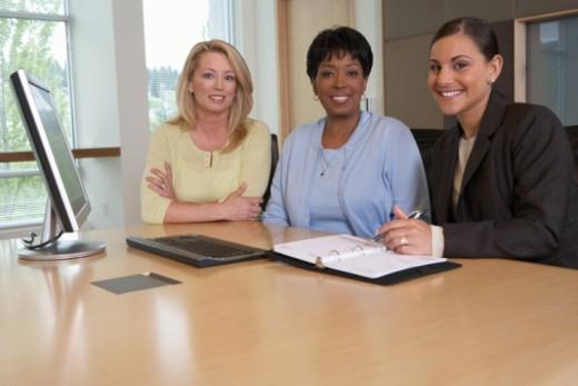 Stock Photo: 1527R-1098376 Three businesswomen sitting side by side in boardroom, portrait