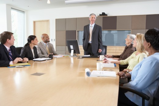 Seven executives meeting in boardroom, smiling : Stock Photo