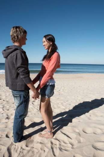 Stock Photo: 1527R-1098737 Teenage couple (16-18) holding hands on beach, smiling at each other