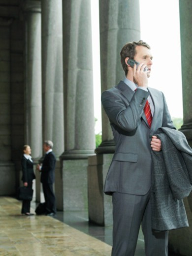 Stock Photo: 1527R-1098753 Businessman using mobile phone, coat over arm, low angle view
