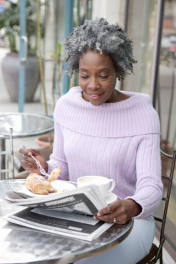 Senior woman having breakfast, reading newspaper : Stock Photo