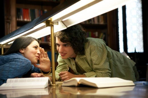 Young woman whispering to young man across table in library, smiling : Stock Photo