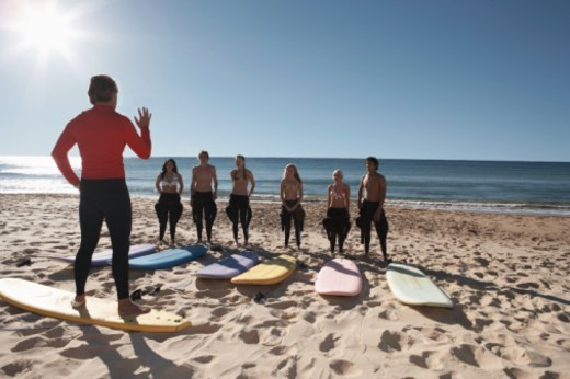 Male surfing instructor on board on beach giving lesson to group : Stock Photo