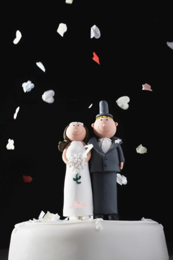 Bride and groom cake decorations being showered with confetti : Stock Photo
