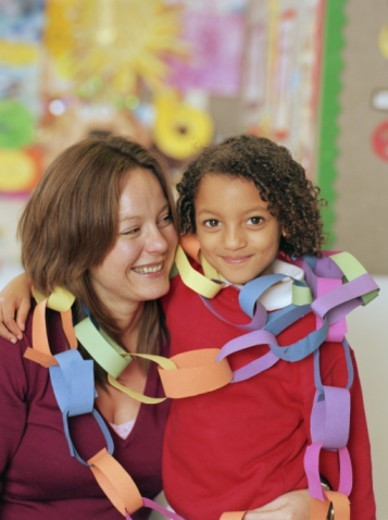 Schoolgirl (5-7) with teacher, wearing paper chains, portrait : Stock Photo