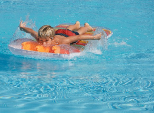 Stock Photo: 1527R-1101491 Boy (6-8) paddling on inflatable raft in swimming pool