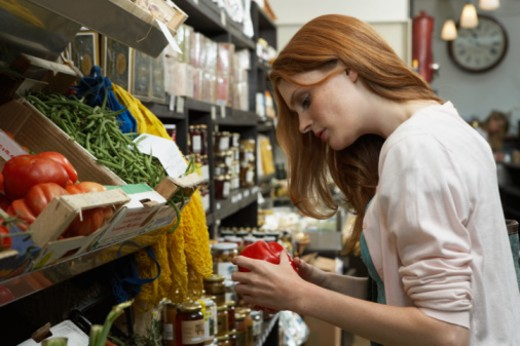 Young woman in shop examining large tomato, side view : Stock Photo