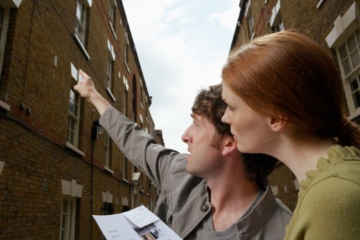 Stock Photo: 1527R-1102085 Young couple in street looking up, man pointing, side view, close-up