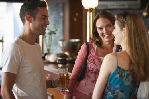 Young man talking to two women at bar, holding glass of beer, smiling : Stock Photo