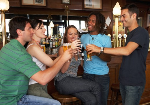 Group of people raising glasses together in bar : Stock Photo