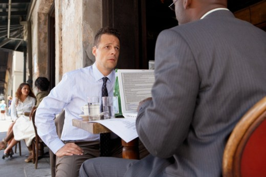 Two businessmen sitting in outdoor cafe : Stock Photo