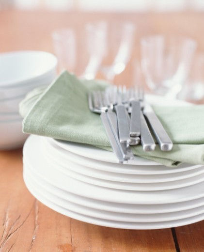 Plates, cutlery, napkins, bowls and glasses (focus on foreground) : Stock Photo