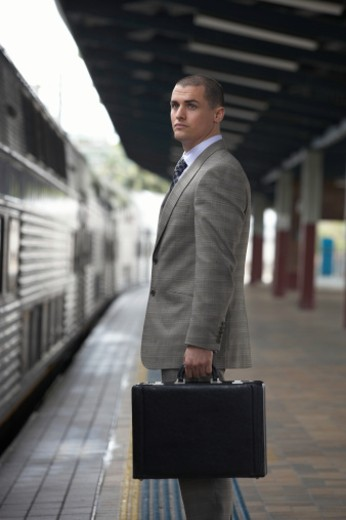 Stock Photo: 1527R-1105031 Businessman standing on train platform holding briefcase