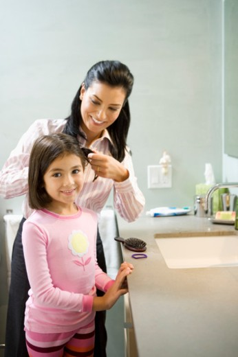 Mother fixing daughter's (5-7) hair in bathroom : Stock Photo