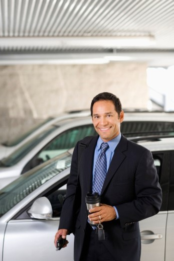 Businessman standing by car : Stock Photo
