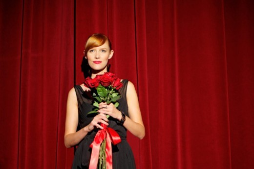 Woman holding flowers on stage : Stock Photo