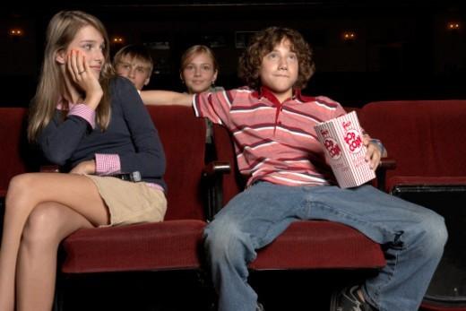 Stock Photo: 1527R-1105505 Teenage couple sitting in movie theatre auditorium