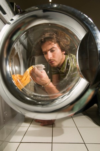 Man pulling out laundry from washing machine, view through door : Stock Photo