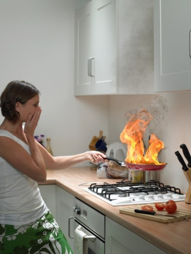 'Woman with hand to face holding burning frying pan in domestic kitchen, side view' : Stock Photo