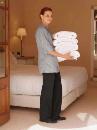 Stock Photo: 1527R-1108549 Maid carrying towels in hotel bedroom, portrait