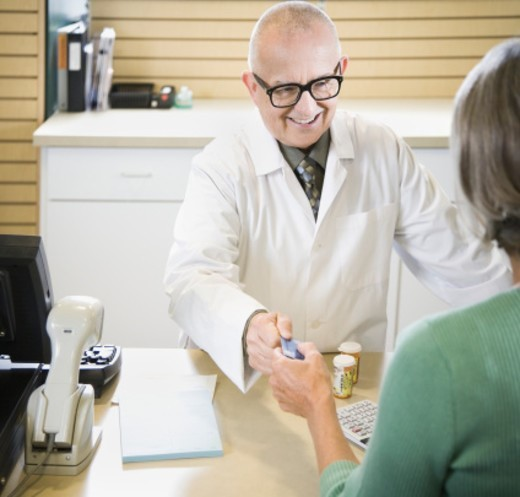 Senior male pharmacist smiling, taking credit card from senior woman : Stock Photo