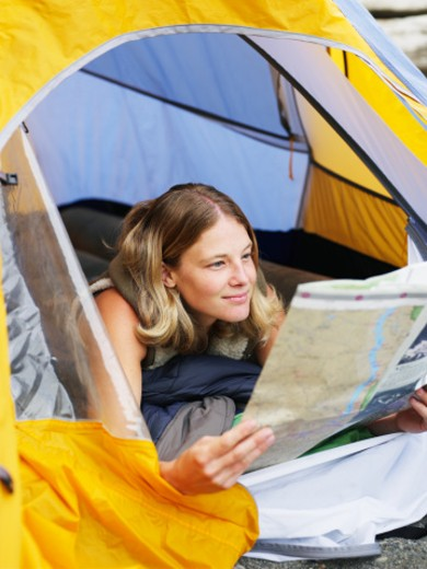 Stock Photo: 1527R-1109163 Young woman lying in tent, looking at map