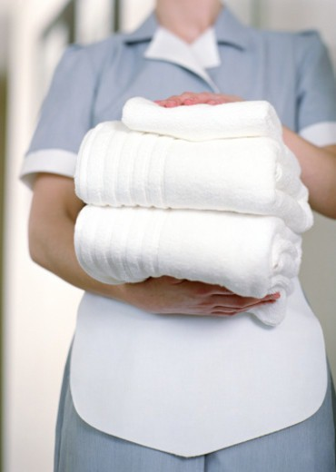 Uniformed hotel maid holding stack of white towels, mid section : Stock Photo
