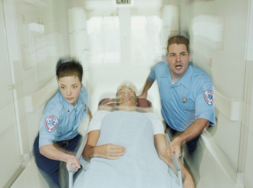 Emergency medical technicians wheeling on patient in stretcher : Stock Photo