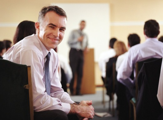 Businessman attending conference, smiling, portrait : Stock Photo