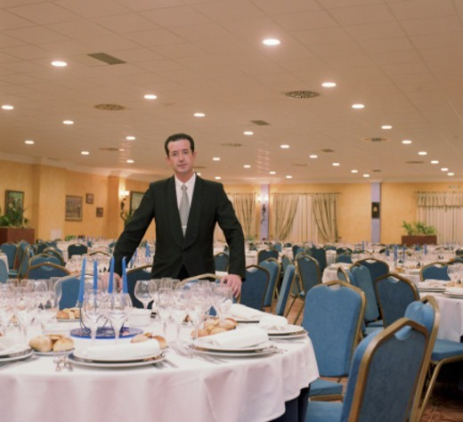 Stock Photo: 1527R-1110477 Head waiter standing beside table in empty banquet hall, portrait