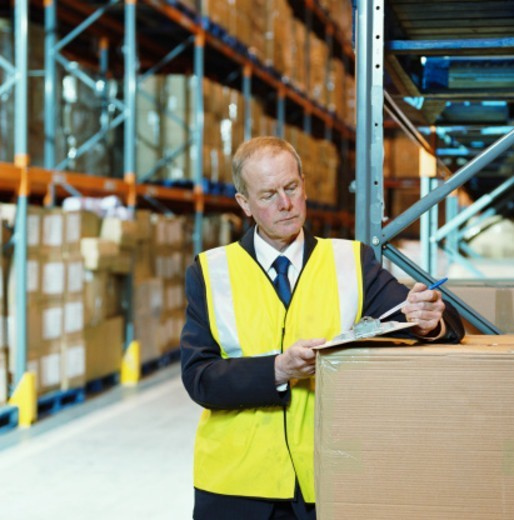Man in warehouse checking clipboard : Stock Photo