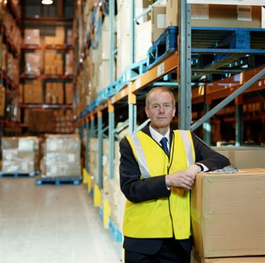 Stock Photo: 1527R-1110748 Man in warehouse leaning on cardboard box, portrait