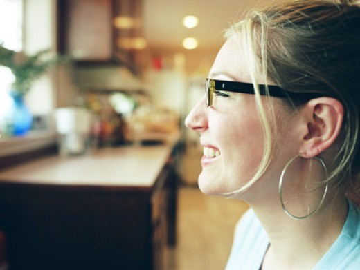 Stock Photo: 1527R-1110821 Young woman sitting in kitchen, profile, close-up