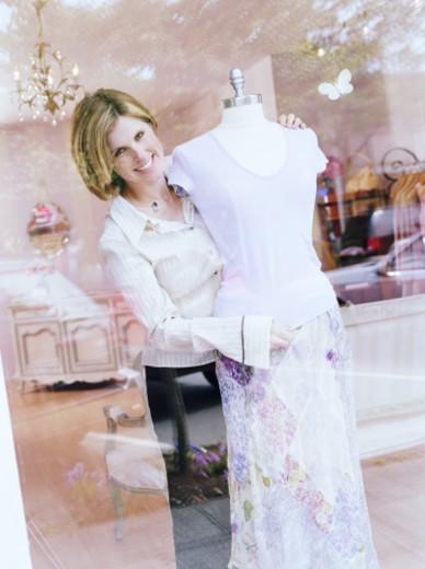 Shop owner adjusting mannequin in shop window, portrait : Stock Photo