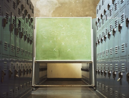 Football play written on chalkboard in locker room : Stock Photo