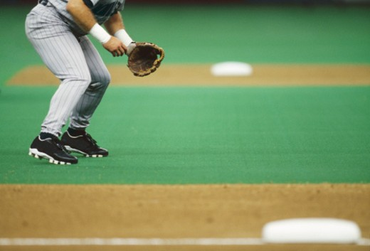 Baseball player standing in infield, low section, side view : Stock Photo