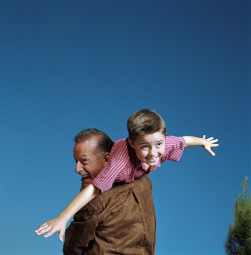 Stock Photo: 1527R-1112807 Boy (6-8) pretending to fly while grandfather holds him over shoulder