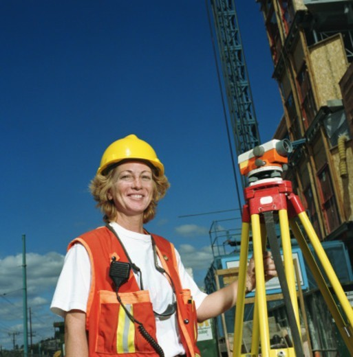 Stock Photo: 1527R-1112923 Woman wearing hardhat, standing next to surveying equipment, portrait