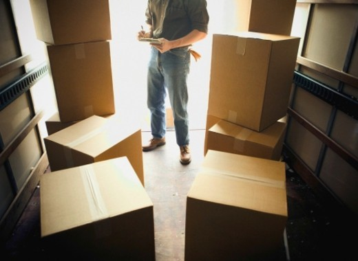 Man in back of lorry with cardboard boxes, using notepad, low section : Stock Photo