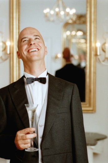 Stock Photo: 1527R-1114127 Man wearing tuxedo, holding champagne flute looking up, smiling