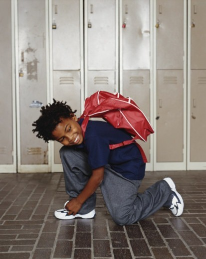 Stock Photo: 1527R-1114144 Boy (8-10) kneeling, tying shoelace, smiling, lockers in background