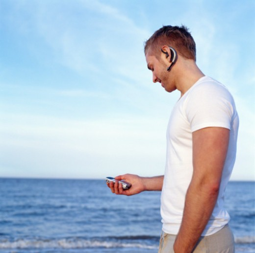 Young man standing by sea, using mobile phone, side view : Stock Photo